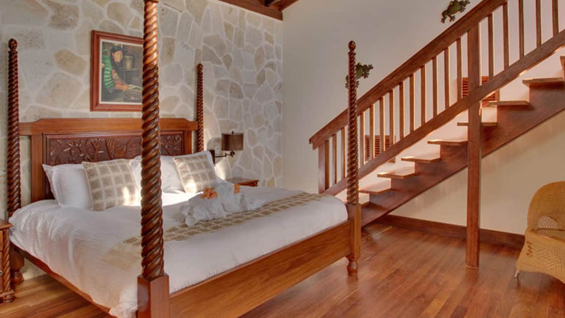 Four-post bed with wood detailing and local artwork adoring the walls, with stairs leading to a sunny balcony at Caves Branch Jungle Lodge in Belize