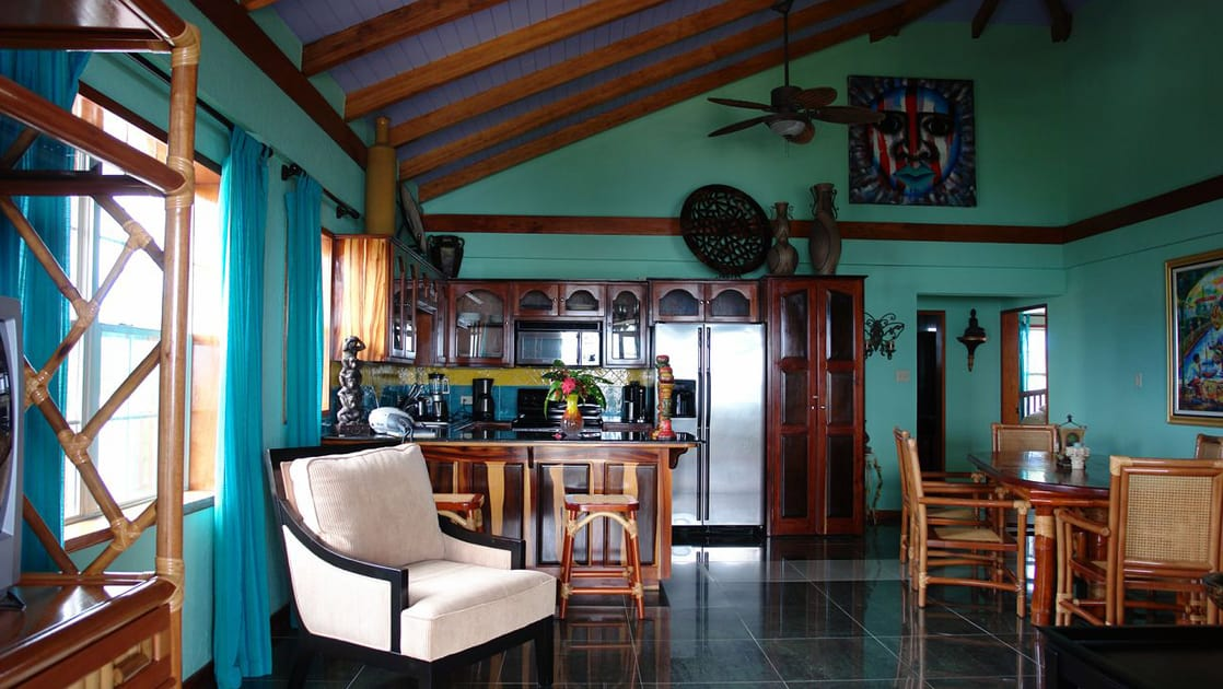 Kitchen and dining area with table for four in cabin at Chabil Mar Villas in Belize