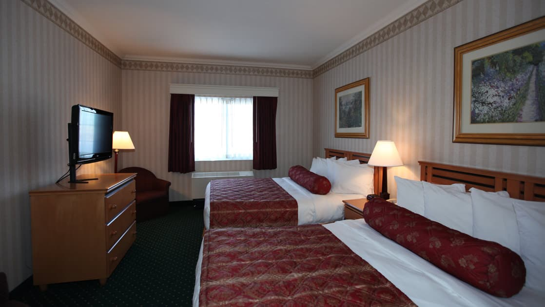 Double room with two beds, dresser, nightstand, reading light and TV at Clarion Suites in Anchorage