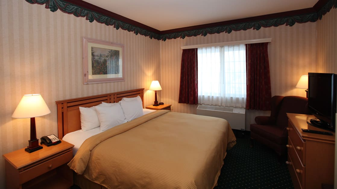 Room with king bed, nightstands, dresser and TV at Clarion Suites in Anchorage