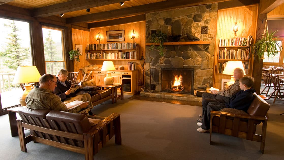 The lobby of the North Face Lodge, a wilderness accommodation in Alaska, with a wood-burning fireplace and comfortable couches. This is a hotel located within Denali National Park.