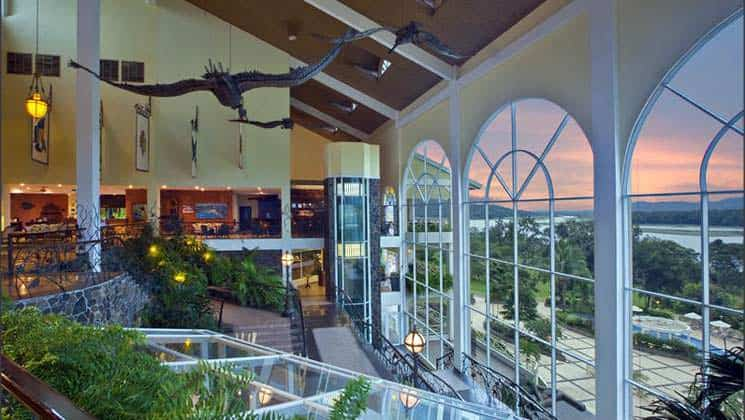 Inside the main lobby of Gamboa Rainforest Resort in Panama, with local plants and wildlife decorations and large windows with rainforest views