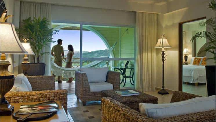 Couple stands on balcony with hammock, table and chairs, with living room with wicker coffee table and three chairs at Gamboa Rainforest Resort in Panama