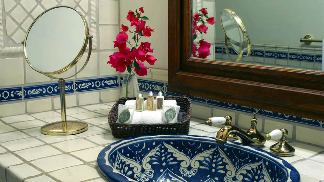 The bathroom of the garden suite, with a blue tiled sink and white tiled vanity, fresh flowers, at Todos Santos Inn, an old hacienda hotel in Baja