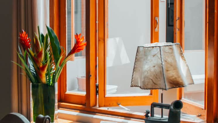 looking out toward the window of the hotel antigua miraflores in peru with a flowering plant in a vase and an old lamp