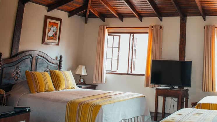 suite room with three beds with yellow and white theme and wooden beams on the ceiling at the hotel antigua miraflores in peru