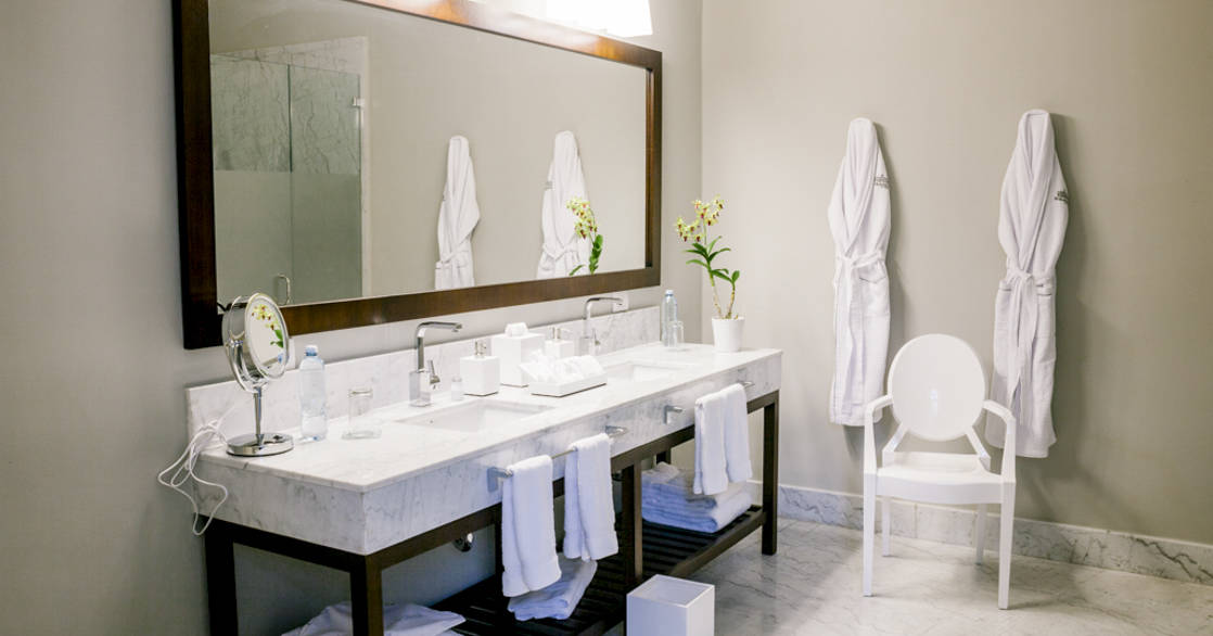 Large mirror, twin sinks and chair in bathroom of Park Suite at Hotel del Parque in Guayaquil, Ecuador