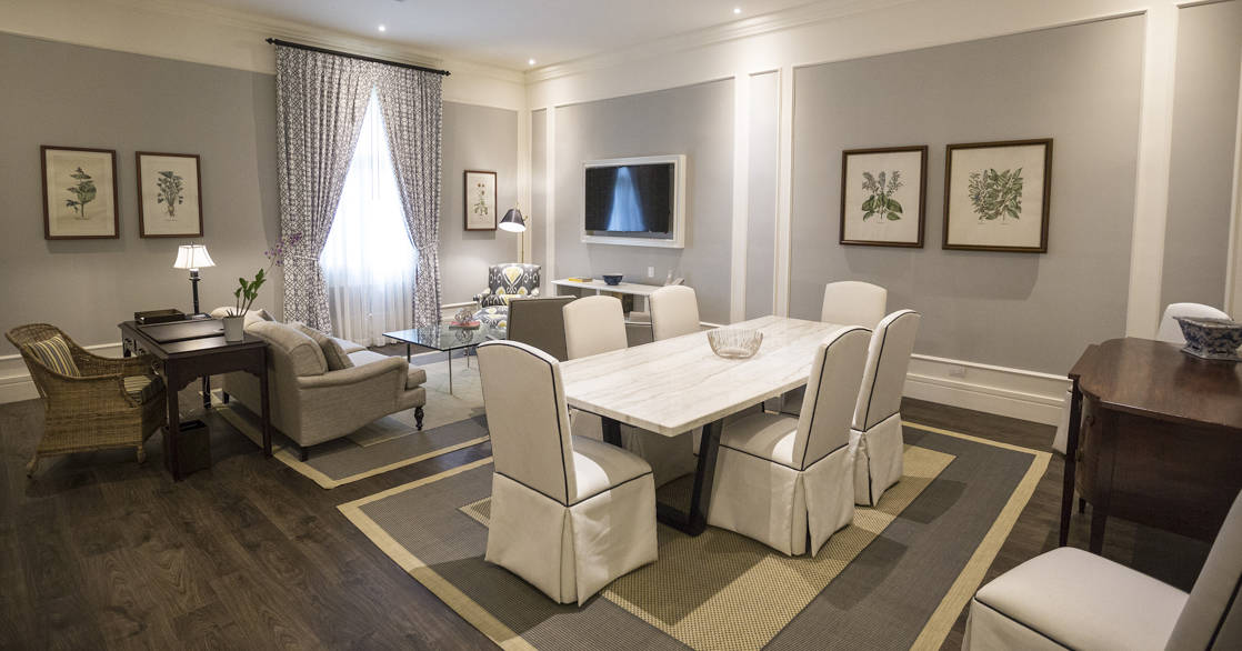 Park Suite interior with dining table and chairs for six, desk, chair, loveseat, coffee table, TV and window at Hotel del Parque in Guayaquil, Ecuador