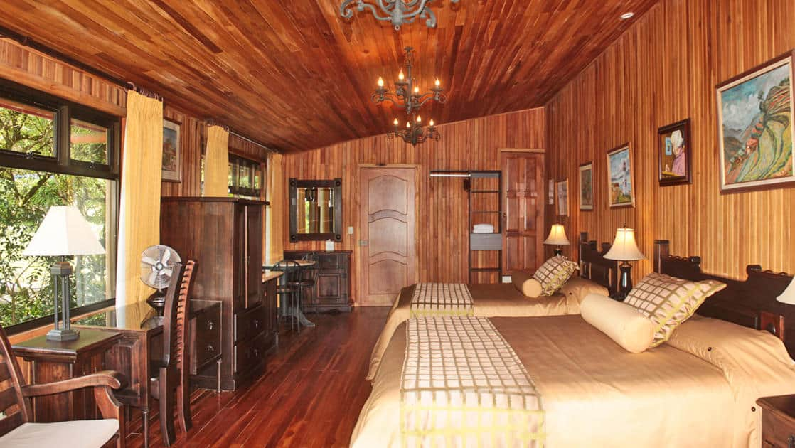 Suite interior with two beds, desk, table and chairs, dresser and wood finishings at Hotel Fonda Vela in Monteverde, Costa Rica