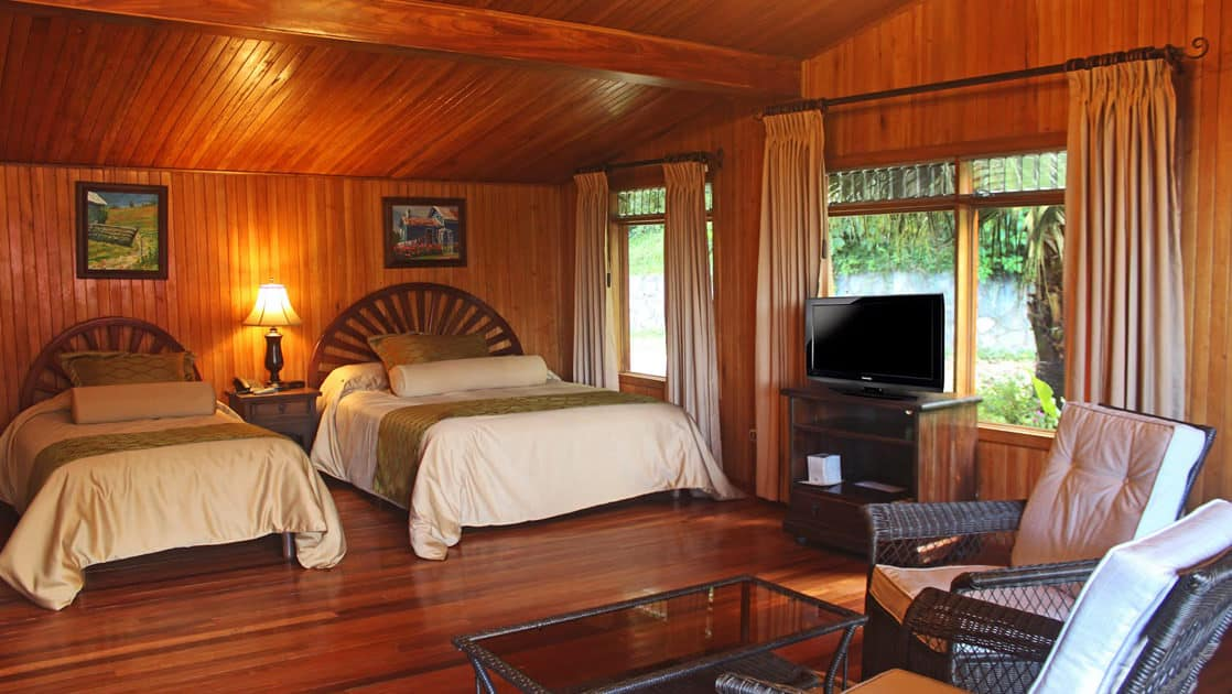 Interior of Standard Room with two beds, table and chairs, TV and windows at Hotel Fonda Vela in Monteverde, Costa Rica