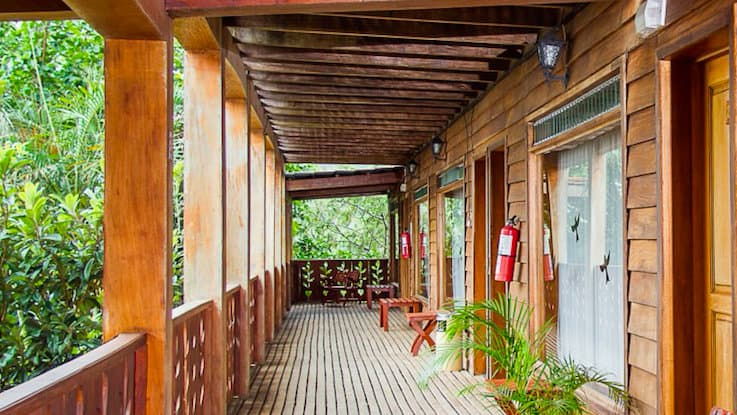 A covered porch in front of the rooms at the Hotel Heliconia in Costa Rica offers guests jungle views and opportunities for birdwatching