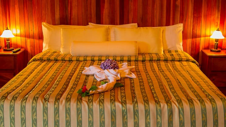 A room at the Hotel Heliconia in Costa Rica's Monteverde region offers home-style comfort, a large bed, fresh towels, and flowers