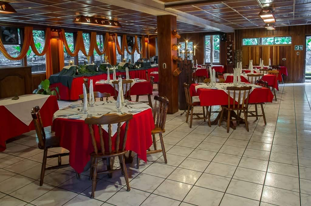 Round tables are set with red tablecloths, fine dining placements, and home-style wooden chairs at the restaurant inside Hotel Heliconia in Costa Rica's Monteverde region