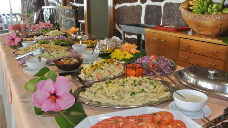 buffet table at hotel iorana easter island in chile with plates of bright fruit, vegetables and prepared dishes