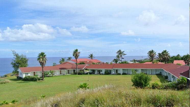 exterior view of hotel iorana easter island in chile with a large lawn around it, sunny skies above and the ocean in the distance
