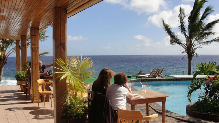 travelers relaxing outside by the pool looking at the ocean with a palm tree blowing in the wind at hotel iorana easter island in chile