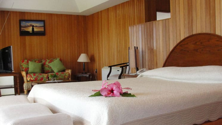 deluxe room with a king bed, wooden walls and flowers on the comforter at hotel iorana easter island in chile