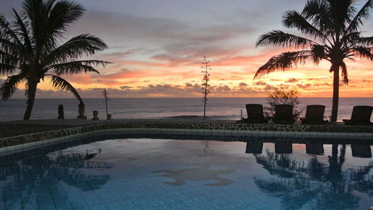 sunset at the pool overlooking the ocean with vibrant clouds and colors in the distance at hotel iorana easter island in chile