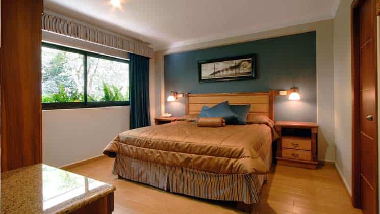 room with king bed with gold quilt, blue wall and picture above it and window on the left at hotel ladera in panama