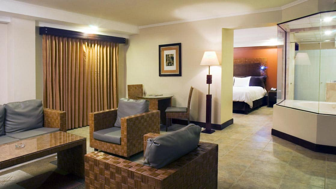 The Grand Spa Suite with a seating area, curtains, and a bed in an adjoining room at the four-star Hotel Presidente, in downtown San José, Costa Rica