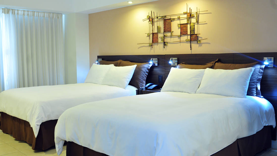 The Standard Room with two full beds, white comforters, and lighting at the four-star Hotel Presidente, in downtown San José, Costa Rica
