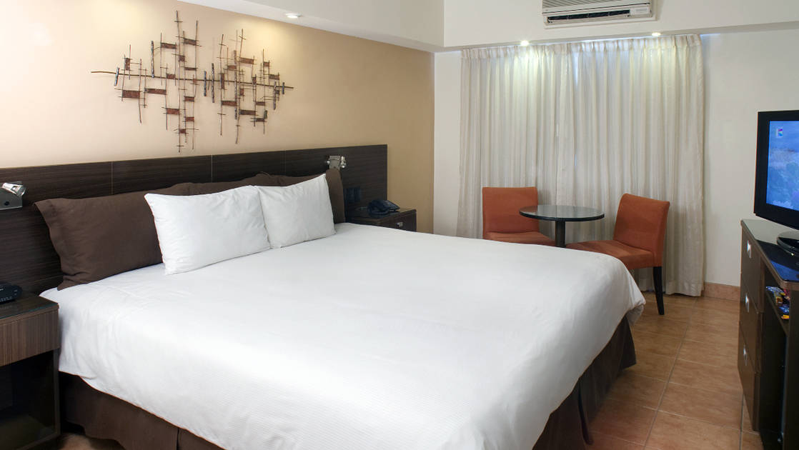 The Standard King Room with a large bed, white linens, and lighting at the four-star Hotel Presidente, in downtown San José, Costa Rica