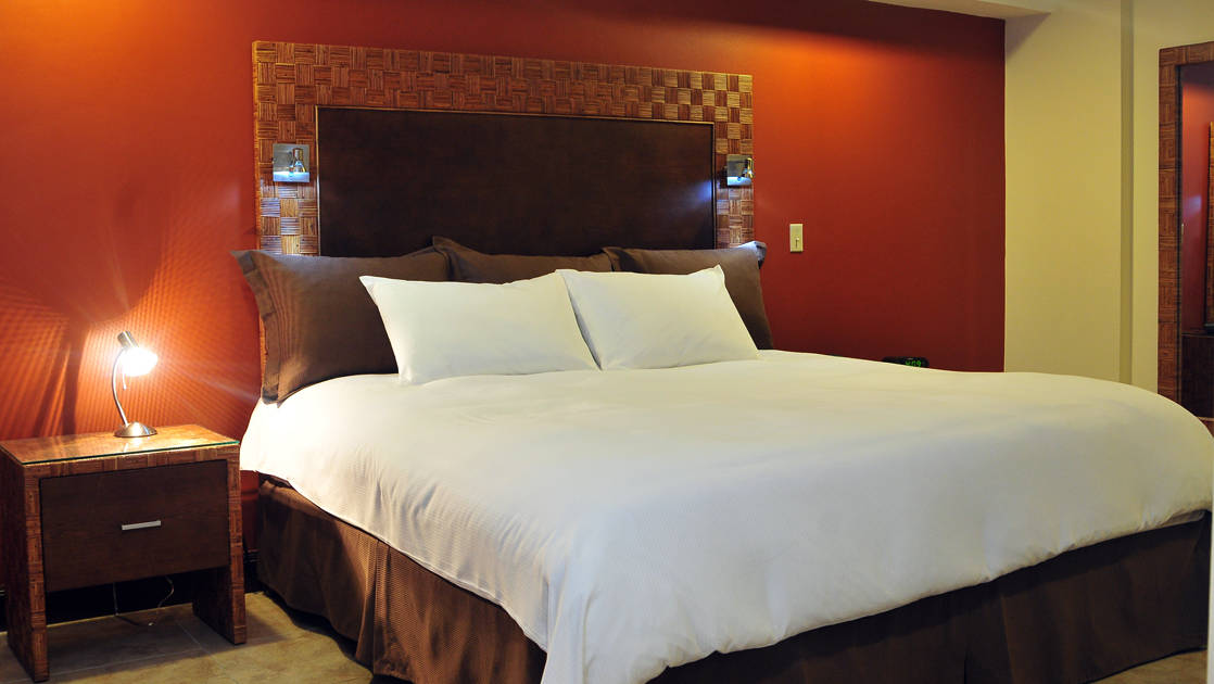 The large bed inside the King Suite with a nightstand and a reading light at the four-star Hotel Presidente, in downtown San José, Costa Rica