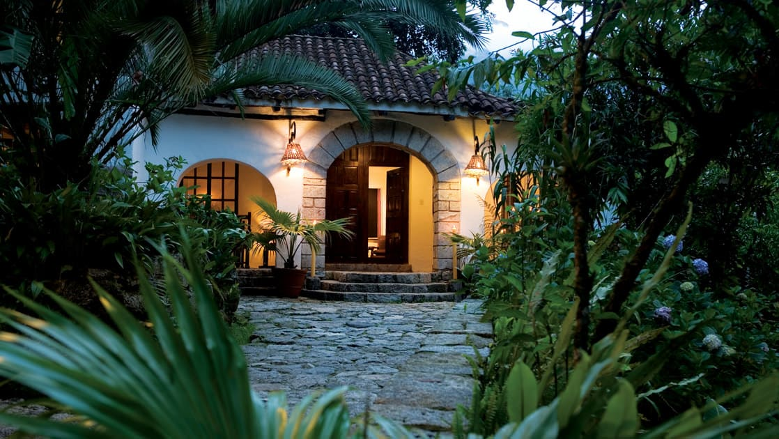 The arched entrance to the Inkaterra Machu Picchu Pueblo Hotel, a National Geographic Unique Lodge of the World in the Andes with 83 whitewashed adobe casitas tucked away in the cloud forest.