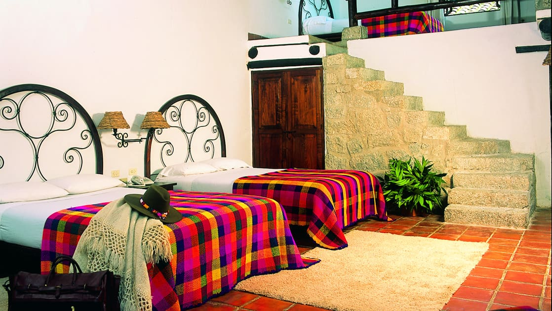 A guest room at the Inkaterra Machu Picchu Pueblo Hotel, with two full beds, Andean style, and furniture made by local artisans, for respite in Peru.