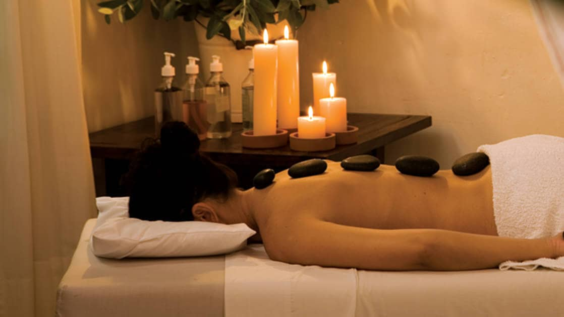 A person lies face down on a massage table with stones placed on their spine, receiving deluxe spa treatment at the Inkaterra Machu Picchu Pueblo Hotel, a National Geographic Unique Lodge of the World