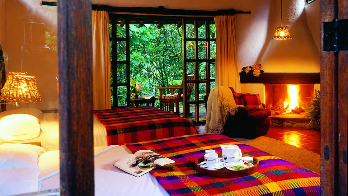 A beautiful room at the Inkaterra Machu Picchu Pueblo Hotel, with a large bed, wooden Andean architecture, a fireplace, and a window looking at the cloud forest in Peru.