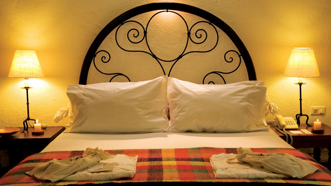 A superior deluxe room at the Inkaterra Machu Picchu Pueblo Hotel, with a large bed, reading lights, a woven blanket, and a bed frame displaying artisanship.