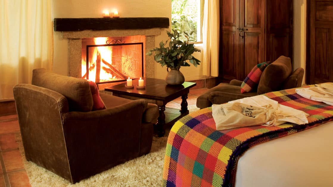 A warm fireplace lights up the superior deluxe room at the Inkaterra Machu Picchu Pueblo Hotel, with a large bed, comfortable chair, woven Andean textiles, and artisan furniture.