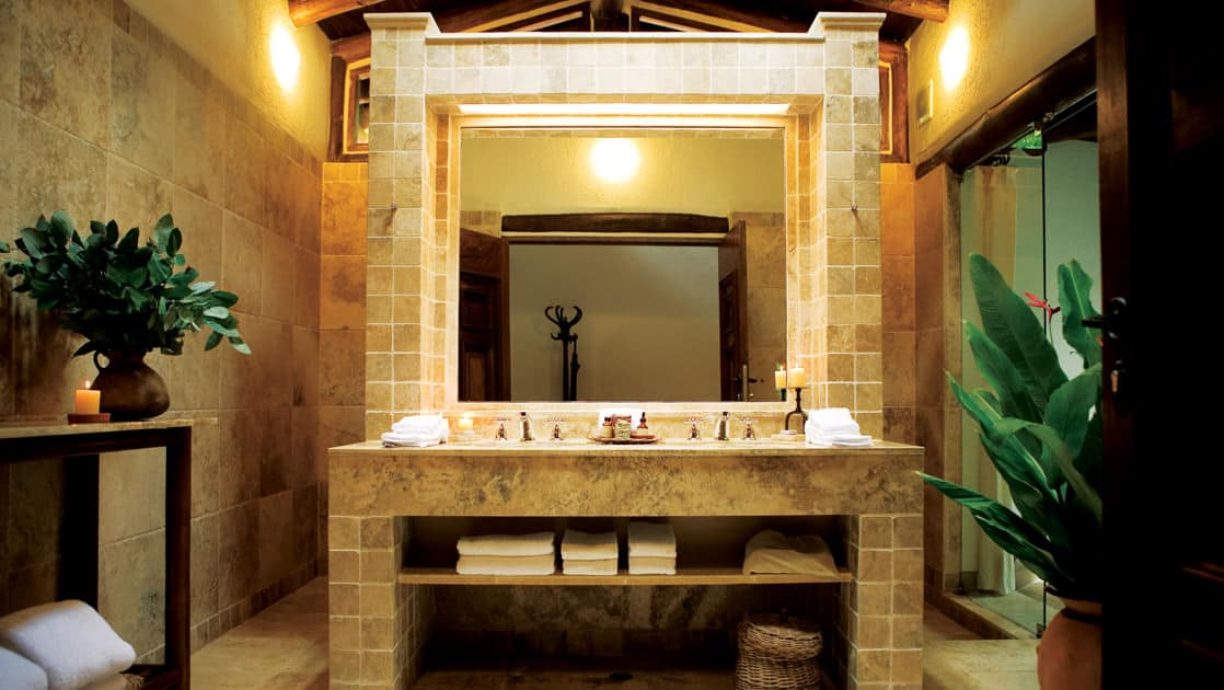 The ornate vanity inside the bathroom at a private villa at the Inkaterra Machu Picchu Pueblo Hotel, with white tiles, fresh plants, a large mirror, and pure spring water.