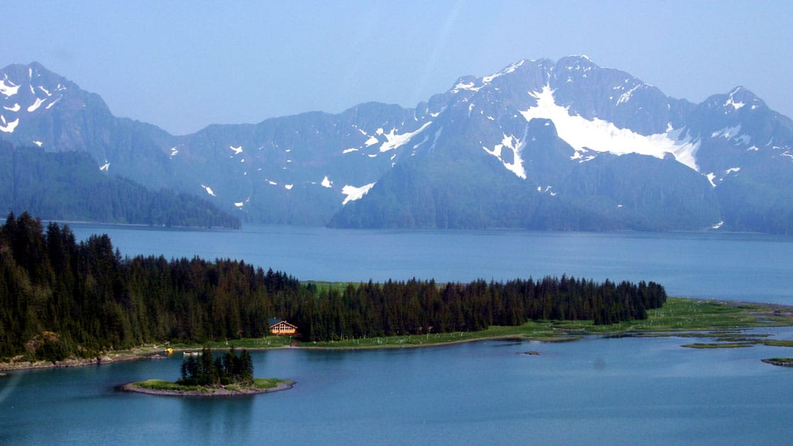 The Kenai Fjords Glacier Lodge is located within the 700,000-acre National Park. A view of the mountains, the Pedersen Glacier, a lake, and the forest where the hotel is nestled.