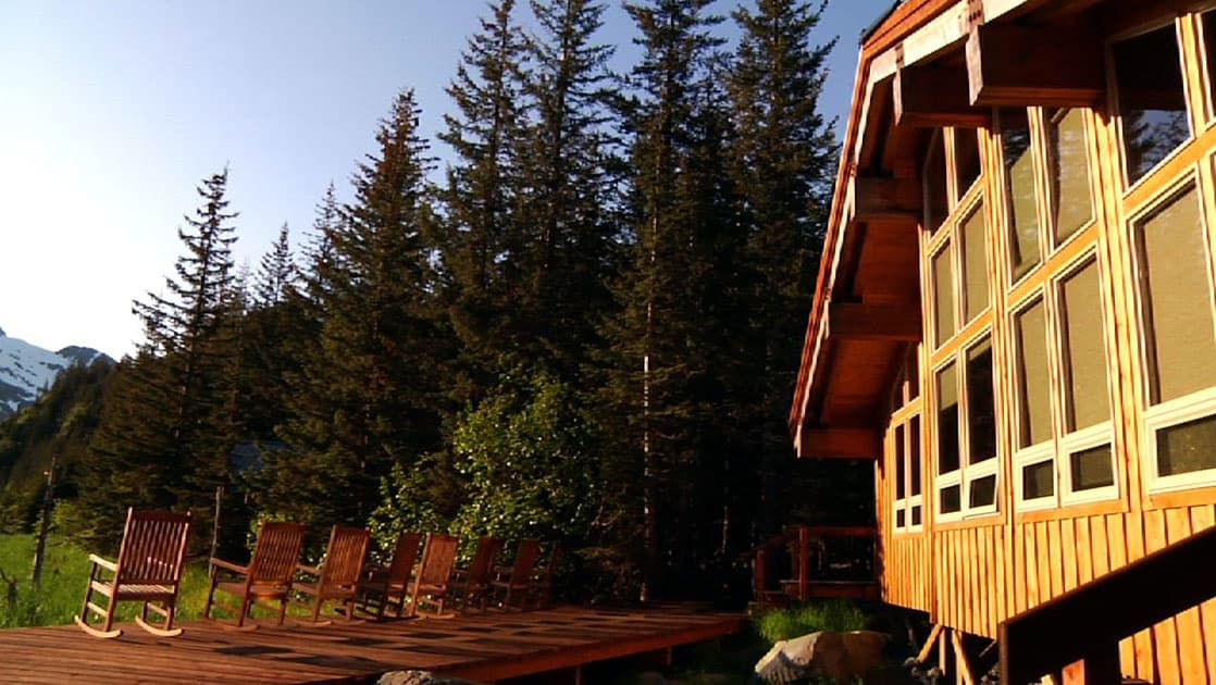 The exterior of the sustainable, eco Kenai Fjords Glacier Lodge, which is nestled in Alaskan forest and offers 16 comfortable log cabins.