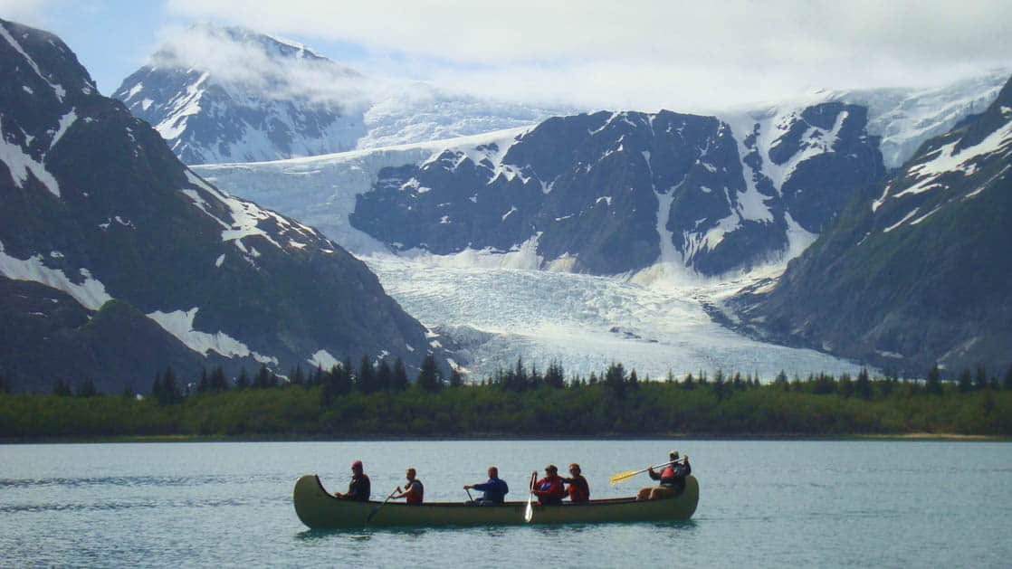 A group of people paddle a canoe through an alpine lake just under a view of the massive Pedersen Glacier in Alaska, near the Kenai Fjords Glacier Lodge
