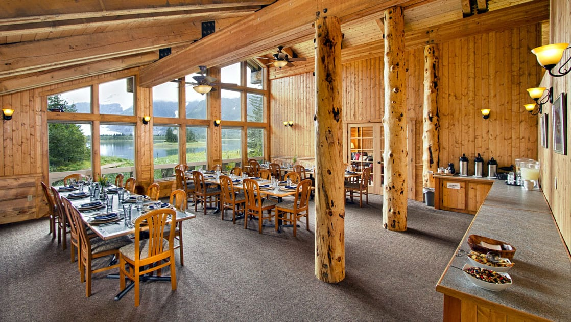 Long wooden tables and chairs are set for a meal inside a room with log cabin architecture and big windows looking toward the forest at the Kenai Fjords Glacier Lodge in Alaska