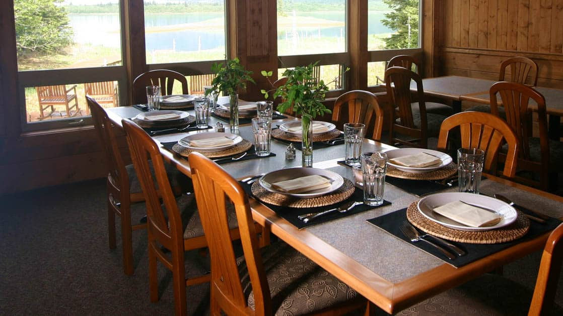 A table is set with fine dining features at Kenai Fjords Glacier Lodge, where chefs prepare fresh, hearty meals with Alaskan seafood, meat, and fare