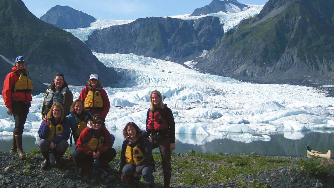 A group of hikers pose in front of the Pedersen Glacier in Alaska, near the Kenai Fjords Glacier Lodge