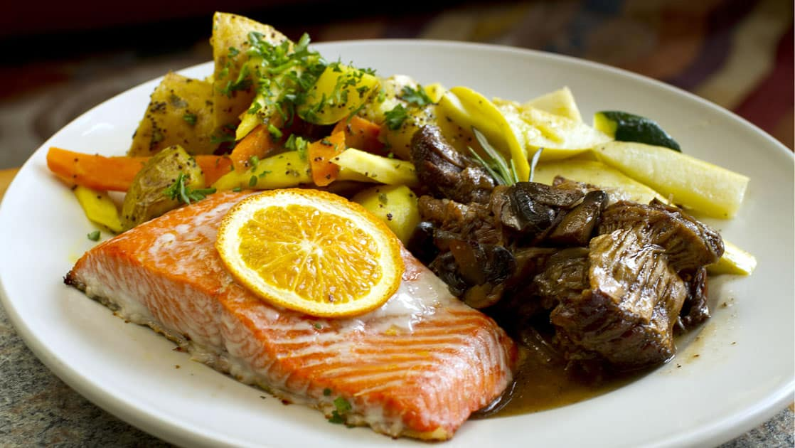 A dish with fresh Alaskan salmon, vegetables, and lemon is plated for guests staying at the Kenai Fjords Glacier Lodge, a sustainable operation in Alaska