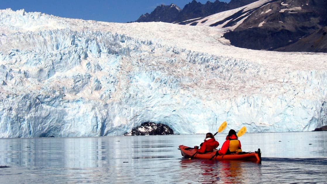 A kayak with two people floats in calm water at the foot of the Pedersen Glacier in Alaska, near the Kenai Fjords Glacier Lodge