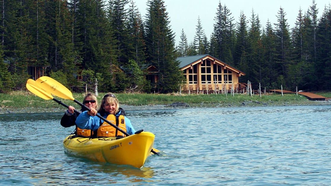 Two people paddle a kayak through calm, clear water just beyond the main cabin of Kenai Fjords Glacier Lodge, nestled in the woods of Alaska