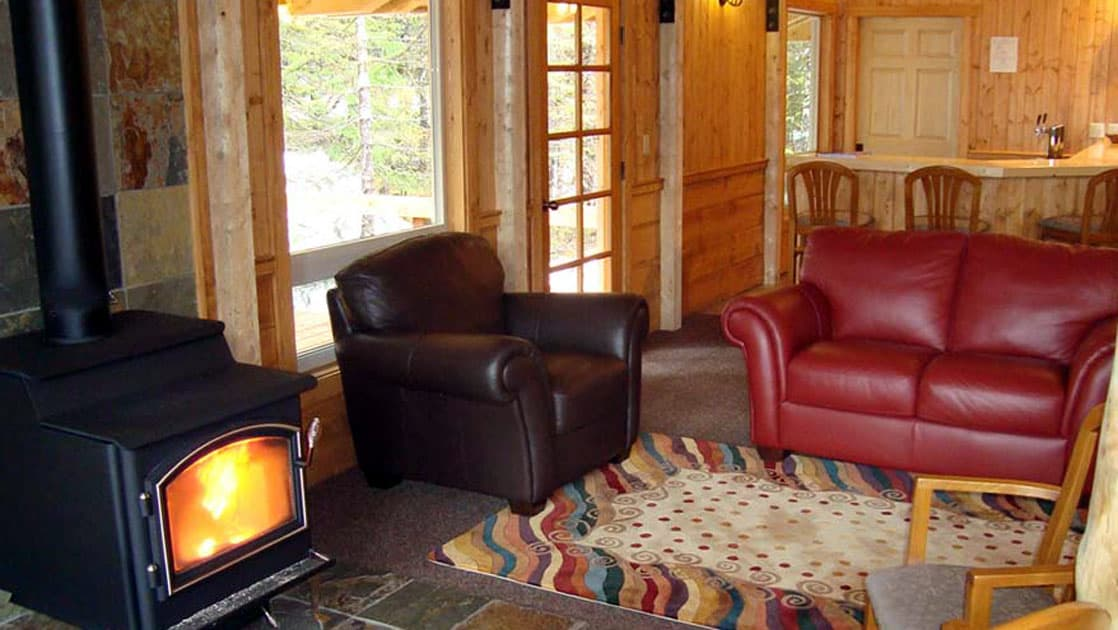 A wood stove warms up the lounge with comfortable leather chairs at the Kenai Fjords Glacier Lodge, a sustainable operation in Alaska.