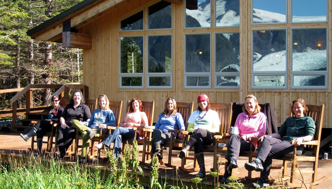 A group of people sit in a row of chairs on the patio outside the main cabin at the Kenai Fjord Glacier Lodge, a sustainable operation in Alaska