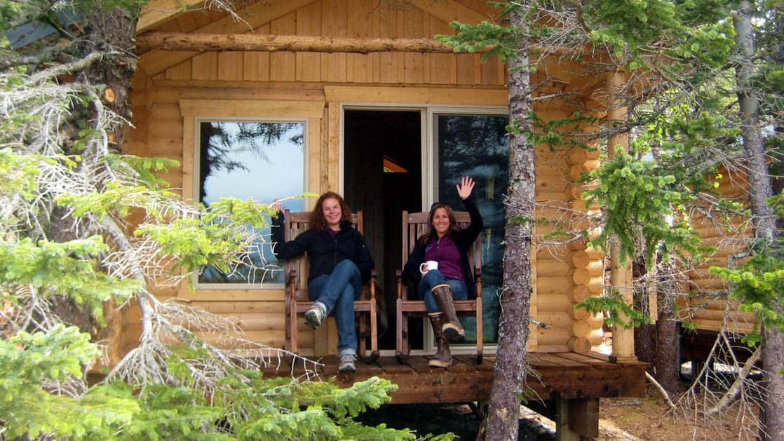 Two people sit on chairs on a covered patio just outside one of the private log cabins at the sustainable, eco resort Kenai Fjords Glacier Lodge in Alaska