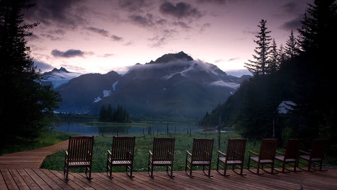 A row of chairs are lined up on the porch with a panoramic view of the mountains and the forest at dusk at the Kenai Fjords Glacier Lodge, a sustainable eco cabin in Alaska