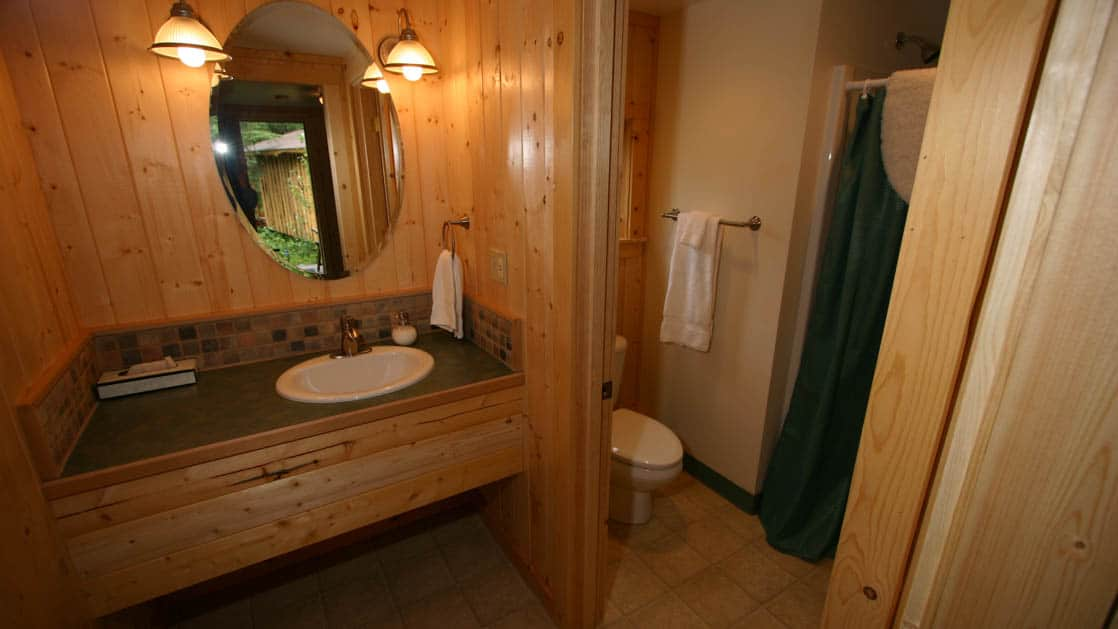 Private bathrooms with a vanity, mirror, toilet, and shower inside one of the guest cabins at the Kenai Riverside Lodge, an ideal home-base for adventure in Alaska