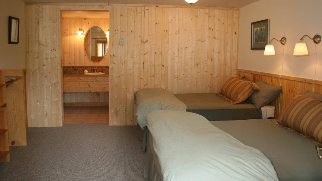 Inside one of the private guest wooden cabins at the Kenai Riverside Lodge, an ideal home base for adventure, with two full beds, reading lights, and a bathroom