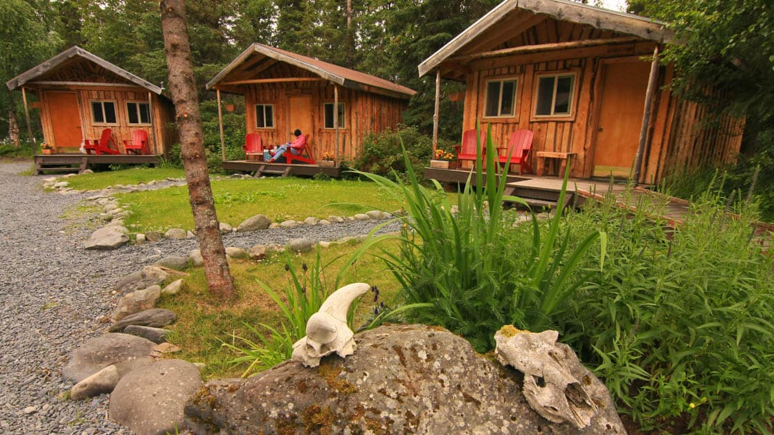 Stone walkways lead up to three private guest cabins with red chairs and a covered porch at the Kenai Riverside Lodge, a nature retreat in Alaska